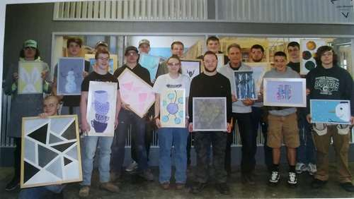 Students at the Capital Area Career Center help Hannah frame her artwork.